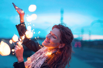 Happy woman playing with fairy light garland at evening closed eyes