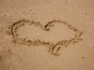 Heart drawn on the sand of the beach.
