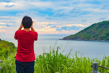 The man standing on the hill and he use his moblie phone to take photo during sunset of ocean view