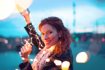 Happy woman with fairy light garland at evening outdoors Wall mural