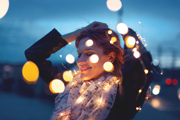 Sensual redhead woman playing with garland fairy lights at night