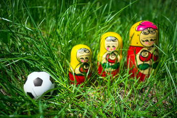 Football soccer ball and three nesting dolls in green.  Winner, championship, competition concept. Selective focus
