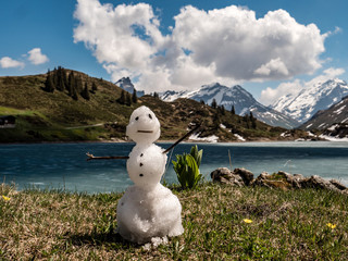 little snowman melting during spring with mountain scenery behind
