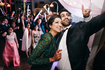 Indian wedding couple takes selfie on the phone standing with their guests in the restaurant