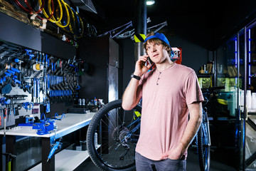 A young, stylish redheaded male small business owner selling and repairing a bike is wearing a blue cap and a pink jersey is using a mobile phone while standing in a bike shop