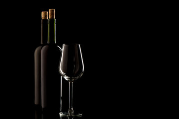 Wine bottles with cork and glass on black isolated background