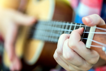 hands playing a guitar close-up