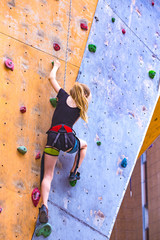 little girl climbing up the wall