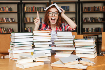 Excited teenage girl sitting at the library table