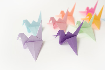 Multi-colored cranes of origami. To put a crane at a lesson of origami