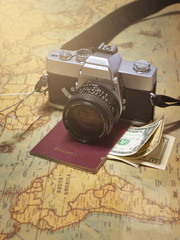Holiday travel background with travel equipment on vintage world map.