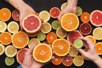 Hands choosing citrus fruits, top view