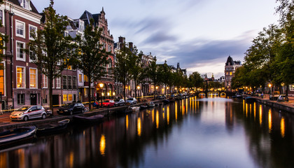 Canal in Amsterdam by night with reflections in the water