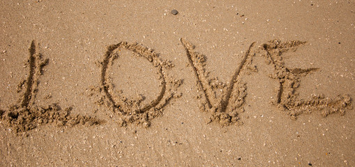 LOVE inscription on the beach sand.