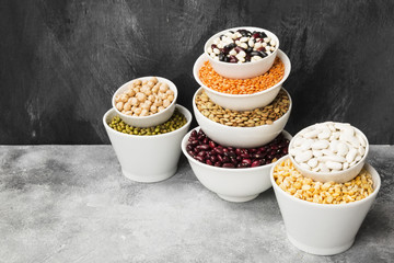 Assortment of beans (red lentil, green lentil, chickpea, peas, red beans, white beans, mix beans, mung bean) on gray background. Copy space. Food background