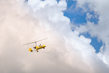 Small helicopter for two person flying on the cloudy sky
