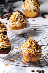 Fresh baked homemade cupcakes with coffee buttercream and caramel standing on cooling rack with eucalyptus branch and coffee beans above over white marble kitchen table.