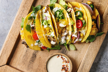 Variety of vegetarian corn tacos with vegetables, green salad, chili pepper served on wooden tray with cream sauce over grey texture background. Top view, space.