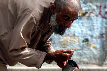 A man splashes his face with water to cool off from the heatwave, along a road in Karachi,