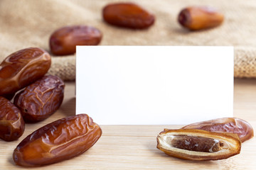 Dates dried fruit with paper white mock up and sackcloth on the wood table background. Creative layout with nature concept with space for text.