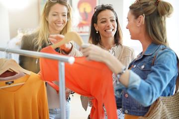 Girlfriends having fun shopping at clothing store