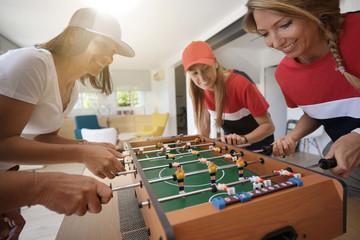 Girls having fun playing foosball at home