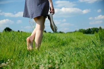 Woman barefoot walk in grass