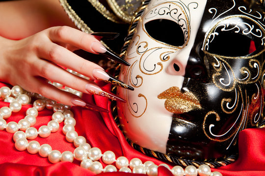 Fashionable nail design with mask on red background
