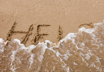 HELP inscription on the beach sand washed by sea wave.
