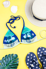 Summer holiday background. Tropical summer concept with fashion accessories, bikini, leaves on bright background.