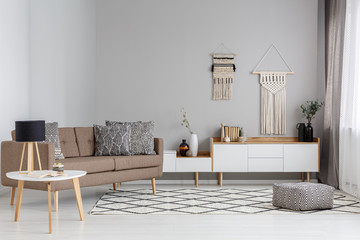 Patterned pouf on carpet near brown sofa in modern living room interior with lamp on table. Real photo