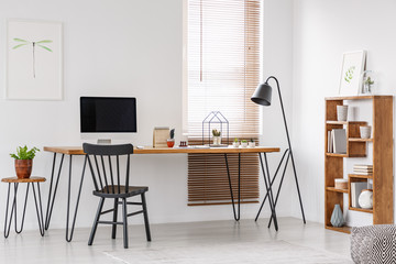 Black chair at wooden desk with computer monitor in bright home office interior with lamp. Real photo