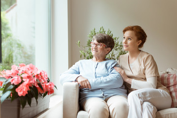 Geriatric woman and her professional caretaker sitting on a couch and looking through a window in a living room. Blooming flowers on a windowsill.