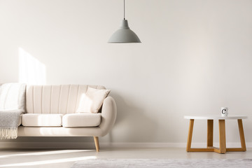 Wooden table near beige sofa in minimal living room interior with grey lamp. Real photo