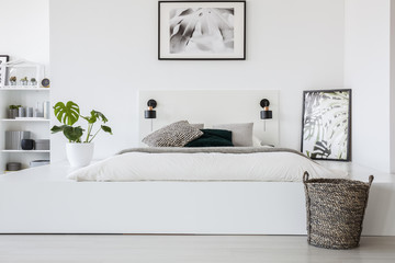 Basket in front of bed on platform with plant and poster in white bedroom interior. Real photo
