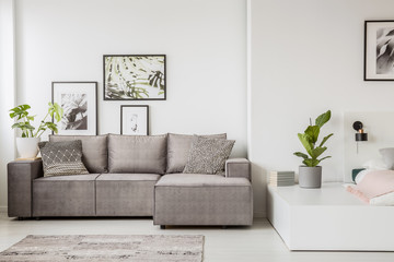 Patterned pillow on grey corner sofa in living room interior with plant and poster. Real photo
