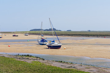 Yachts rest on the rippled sand in an estuary at low tide.