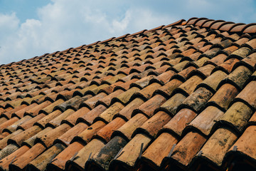 Diagonal rows of orange clay roof tiles on Mediterranean town with blue sky copy space.