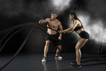 Woman and men working out with battle ropes