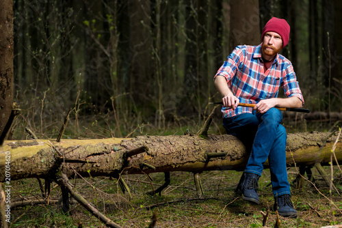 8228d321d80 portrait of a forester in a plaid shirt with an ax sitting on a log ...