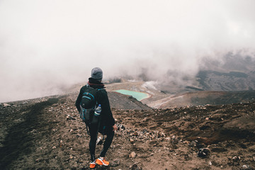 young male adult hiking with misty weather in the mountains