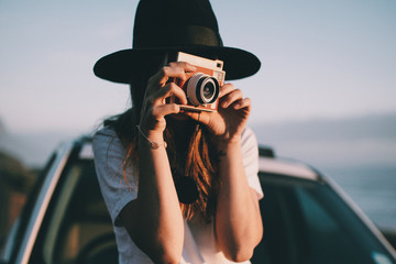 young woman taking picture with retro camera on roadtrip
