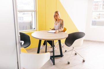 tattooed busy business woman writing notes in meeting room