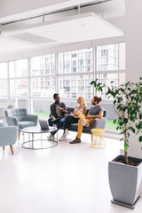 three adults having buisness meeting in big office