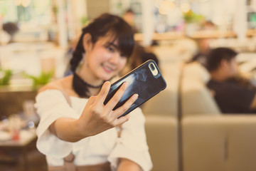 Selective hand pretty girl holding and taking selfie from mobile phone.Asian woman take a photo by smartphone.