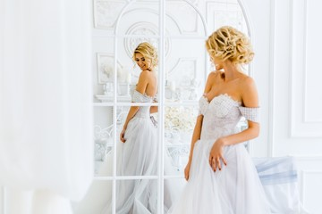 A bride with hairstyle and make up in gougeous wedding dress preparing for the wedding. A portrait of beautiful girl with blond hair and blue eyes in studio with flowers