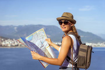 traveling woman holding the map, tourist look on map in historical landmark, travel concept, mountains sea and city on background.