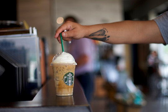 Nikko Harris, 28, places a straw in his iced coffee, before more than 8,000 branches nationwide will close this afternoon for anti-bias training, in Philadelphia, Pennsylvania