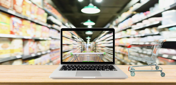supermarket aisle blurred background with laptop computer and cart on wood table online shopping concept