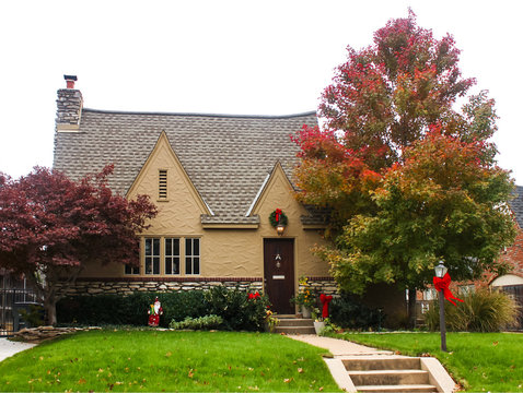 Stone and stucco cottage with autumn leaves a Japanese maple and Christmas bows and wreaths